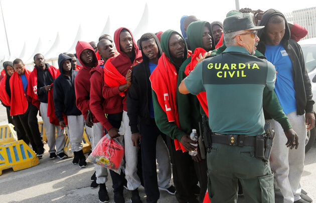 Migrants are stopped by a Spanish Civil Guard as they are led into police buses as they leave the port of Algeciras